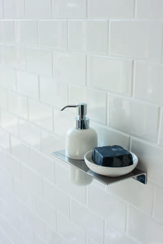 Minimalist accessories for a minimalist, modern bathroom - Stainless steel shelf with ceramic soap dish and ceramic soap dispenser from Britton Bathrooms.