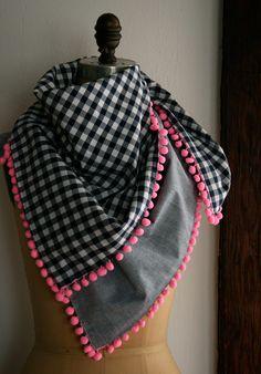 Idée de motifs et couleurs pour une écharpe en tissu bordée de pompons.