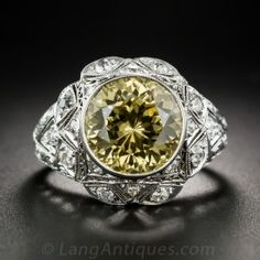 Dazzlingly different! In place of a big fancy yellow diamond, we find a fabulous, bright canary yellow Zircon - clocking in at 11.40 carats. The exotic gemstone sits in an original Art Deco mounting, hand-fabricated in platinum - circa 1920s-30s. The extraordinary, multi-layered, high-profile ring is intricately ornamented with individual geometric settings for the diamonds, delicate milgraining and hand engraving.