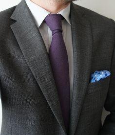 Dark grey herringbone jacket, white shirt, purple tie.