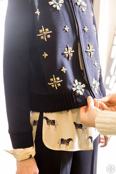 Brooch-like embellishments were hand-stitched to form the pattern on this wool bomber jacket #toryburchfall2014 #nyfw