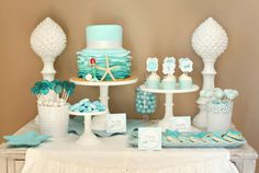 "At her daughter's mermaid-inspired party, Kim Stoegbauer of The TomKat Studio commissioned a showstopping cake. ""The aqua blue ruffle cake was made by my local cake designer, Melissa from Decadent Delights, and my mom and I embellished it with ribbon, a pearl necklace, a starfish, and a little mermaid doll. I placed the cake on one of our white milk glass cake stands filled with raw sugar to create the look of sand."" Source: The TomKat Studio"