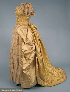 """Ballgown. 1880s. 2 piece, ribbed bright yellow w/ beige satin floral silk brocade, bodice front lacing, low center front point w/ bows, lace cap sleeves & neckline flounce; skirt front w/ 6 tiers of lace flounces, skirt sides draped in beige satin, accordion pleated backbustle, trained skirt w/ padded hem, full lining, built-in bustle petticoat, B 36"""", W 22.5"""", Skirt L 40""""-57"""","""