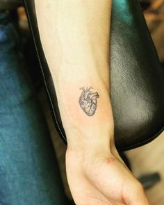 Fine line anatomical heart tattoo on the left inner wrist.