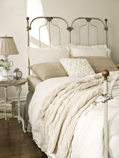 What a calming place to dream...and I love the iron bed, knitted throw, and stack of books...