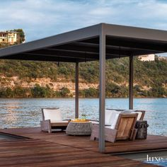 Relaxation is complete on the swim dock thanks to a sofa and armchairs, both by Carlos Motta from Espasso in New York, covered in Sunbrella linen. B&B Italia's Canasta coffee table is the centerpiece under a metal awning fabricated by Dennis Steel.