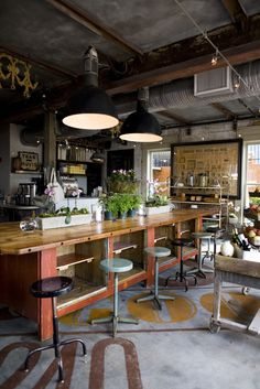 Exposed Concrete Floors, Oversized Lights, timber and greenery make this space magical-The Perish Market in Atlanta Ga.