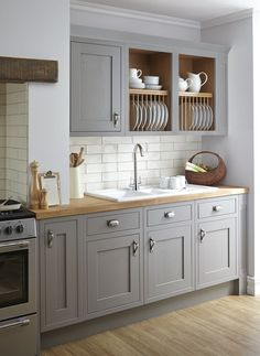 Butcher block countertop and wooden plate rack warm up this gray and white kitchen.