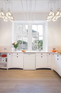 A bespoke Charles Rennie Mackintosh kitchen commissioned by a private client in Edinburgh, Scotland.            - Designed and handmade in Edinburgh by Robin J Horn Furniture & Design, 2015.  White painted ash cabinetry with bleached Ash worktops, hand carved detailing, and custom made lighting and tiles.  Contact: robinjhorn@yahoo.co.uk - for further enquiries.