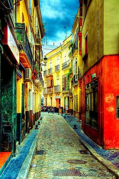 Colourful street in Seville, Spain This looks like something out of a book illustration doesn't it?  http://www.travelandtransitions.com/our-travel-blog/andalusia-2011/andalusia-travel-the-wonders-of-seville/