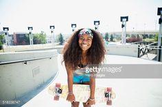 Portrait of teenage girl holding skateboard