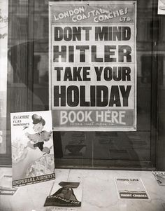 Poster in a London travel agency advising people to book their holidays in spite of the tense situation in Europe (Hitler, Germany, the Second World War). About 1939