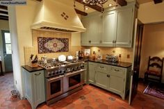 medium gray green cabinets with Mexican tiled floor
