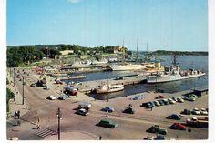 Oslo  Rådhusbryggene, Utstikker A til D (fra venstre) med orlogsfartøy, seilskute, Bygdøyferge. Nordre Akershuskai med fraktefartøy. Buss. Biltrafikk over Rådhusplassen langs bryggene ca 1960