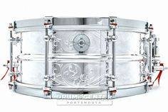 """Dunnett Classic 2N Modeling Aluminum snare drum with patented """"hybrid edged"""" shell (flanged top, unflanged bottom), 8 chromed tube lugs, hypervent,  R4 snare strainer, cold rolled hoops and finished with an engraved scroll design by John Aldridge."""