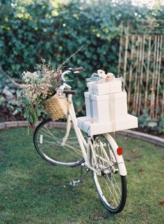 Flowers in the front basket and pretty white presents on the back of a bike
