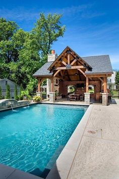 Play in the swimming pool and then relax in the beauty and comfort of this timber frame pavilion accented with metal truss plates. A dining table, fireplace and outdoor kitchen ensure you will enjoy the outdoors in style. From Heavy Timber Truss & Frame