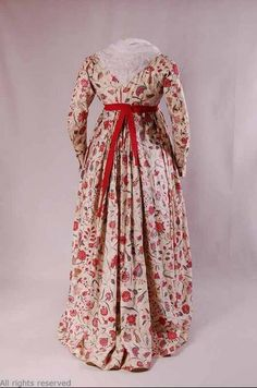 (1790-1800) dress with fichu at the neckline. The skirt falls tight pleats into a slight sweep along the hemline.