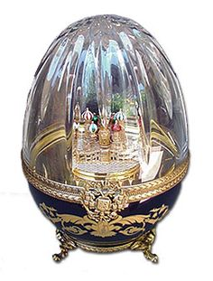 St. Basil's Cathedral Musical Egg. The lower half of the Egg is Limoges porcelain hand painted in midnight blue with decor of gold leafy arabesques.The upper half of the Egg is hand cut crystal in a single large sunburst that centers at the crown of the Egg. The cut crystal top makes it possible to see the Cathedral even when the Egg is closed. The clasp is a medallion of the Romanov double headed eagle insignia. The melody played by the music box is a theme from Beethoven's Ninth Symphony.