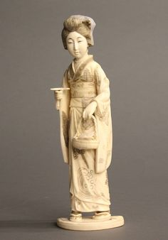 An ivory geisha in kimono by Tamano. Circa late 19th century. Signature on base: Tamano. A geisha in kimono with Maru Mage hairstyle, holding a flower basket and a leaf in her hands. Assembled design. 14 1/4""