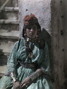 Africa | Tunisian Girl Adorned in Jewelry Sits Against a Wall by Jules Gervais-Courtellemont (1863~1931)