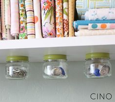 Baby jars screwed onto the underside of a shelf.  Brilliant idea for storing small things in office or bathroom.