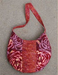 "The ""Rita"" Bag Pattern by Abbey Lane Quilts at KayeWood.com has a rouched center panel which accents the great large print design.  Two big pockets inside make it easy to organize.  It also has a magnetic closure. http://www.kayewood.com/item/Rita_Bag_Pattern/2950 $10.00"