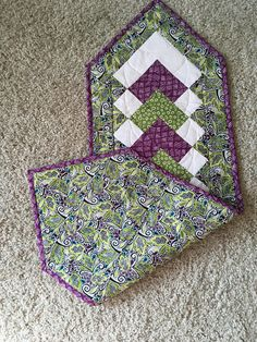 This is a table runner made out of cotton fabric with thin batting between front and back, It is quilted and colorful. The colors are white, green, and purple. It is 13 inches wide and 40 inches long from point to point.