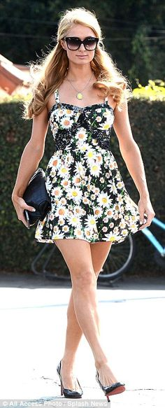 Work it, girl! The 32-year-old playfully pulled on the hem of her pretty daisy-printed dress as she strutted into the eatery in black patent...