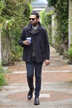 Shop this look on Lookastic:  http://lookastic.com/men/looks/brogue-boots-jeans-pea-coat-gilet-longsleeve-shirt-sunglasses/6889  — Black Leather Brogue Boots  — Black Jeans  — Charcoal Pea Coat  — Dark Brown Quilted Gilet  — Grey Check Long Sleeve Shirt  — Dark Brown Sunglasses