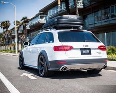 White Audi Allroad with roof rack and black wheels