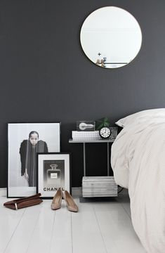 charcoal walls + round mirror + block lamp + layered frames