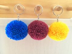 Set of 3 handmade wool pom pom keyrings. As with all our products pom pom keyrings can be made to order in any colours you choose, just specify your colour on ordering. Each pom pom is approximately 5cm in size. They make ideal bag charms. Due to the handmade nature the keyrings should be handled with care to avoid losing any wool.