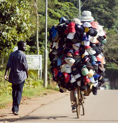 typicalugandan:  A travelling hat salesman riding his bicycle carrying his goods. Kampala, Uganda.  Photographed by gipukan (rob gipman)