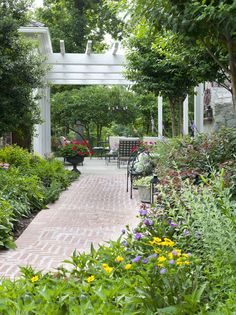 At Cindy and Mark McNair's garden retreat, a brick path connects the side garden to a backyard patio and pergola. Crape myrtles and sun-loving perennials, including purple coneflower, Lilyleaf Ladybells, Coreopsis and Stoke's aster, line the walkway.