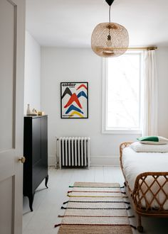 A small guest bedroom is outfitted with the Pari Rattan Daybed from Anthropologie, an old Ikea dresser, an Ikea Tilst Rug, and a Bamboo Pendant from Couleur Locale in France. Celia and Rodolphe bought the Calder poster at the Maeght Foundation in Saint Paul de Vence.