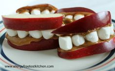 """This kid-friendly snack is a perfect after school treat for your little ones. This three-ingredient recipe for Apple """"Teeth"""" Snack is a simple, fun way to get your children to eat their fruits. Peanut butter is the glue that holds this snack together, but you can substitute sunflower seed butter for it if there's a nut allergy in your family. This is a great recipe for kids with celiac disease."""