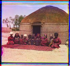 Группа из одиннадцати взрослых и детей сидит на ковре перед юртой — Просмотр —…