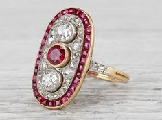 Antique late Edwardian ring made in 18k yellow gold and platinum. Set with two old European cut diamonds weighing approximately .50 carats total. Also set with an old European cut ruby weighing approximately .35 carats. Accented with rubies and rose cut diamonds. Circa 1920. This ring hints at the Deco style to come, but is ornately decorated with rose cut diamonds and contrasting center stones. Diamond and gold mining has caused devastation in areas such as Africa, wreaking havoc on…