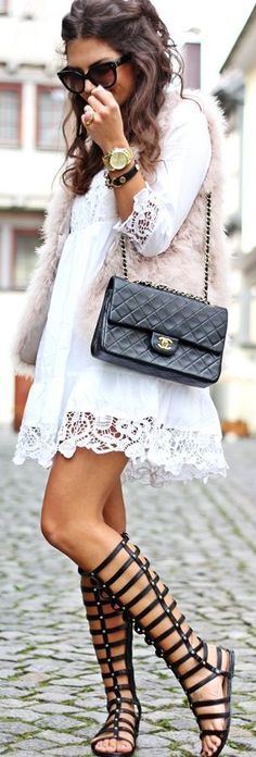Tall black gladiator sandals toughen up a lacy white spring dress