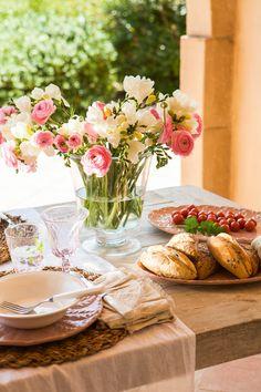 Detalle de mesa de comedor de exterior con caminos de mesa, vajilla blanca, individuales de fibra y jarrón con flores