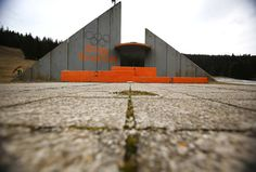 """A concrete podium for winners with the text """"Winter Olympic Games 1984"""" stands abandoned at Mt. Igman, near the Bosnian capital of Sarajevo."""