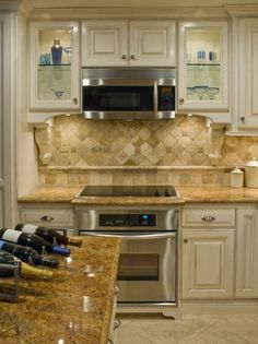 Love how they placed the oven below & the creamy cabinets with maple glaze, yummy!