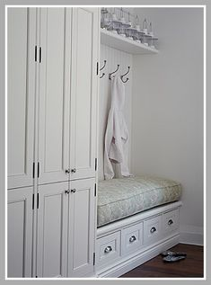 Fantastic mudroom with built-in locker storage. White raised panel mud room cabinet doors and built-in mudroom bench with beadboard backsplash. Mudroom bench with floral bench cushion and wall hooks. Mudroom Storage Bench, Entryway Storage, Built In Storage, Locker Storage, Entryway Bench, Mudroom Cubbies, Storage Benches, Linen Storage, Entryway Ideas
