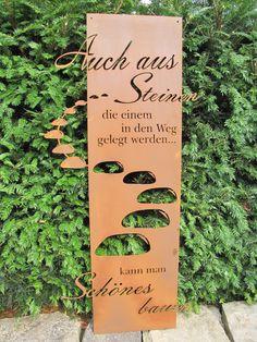 """Edelrost Gedichttafel """"Steiniger Weg""""  Die Tafel ist aufwändig gestaltet, mit vielen Buchstaben die aus der Spruchtafel herausragen.  Die Spruchtafel ist ein Hingucker in jedem Garten und zieht gerade in Vorgärten die Blicke auf sich.  Spruch auf der Tafel lautet:  """"Auch aus Steinen, die einem in den Weg gelegt werden, kann man schönes bauen.""""  Größe:      Höhe: 120 cm     Breite: 55 cm  Preis: 62,- €"""
