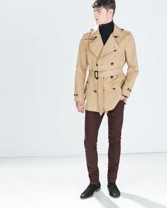 Shop this look on Lookastic:  http://lookastic.com/men/looks/black-turtleneck-tan-trenchcoat-burgundy-jeans-black-chelsea-boots/9368  — Black Turtleneck  — Tan Trenchcoat  — Burgundy Jeans  — Black Suede Chelsea Boots