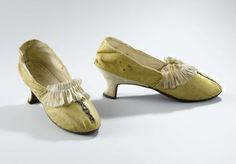 Pair of ladie's shoes, probably The Netherlands, c. 1760 - c. 1775. Yellow silk on top embroidered with a band of silver sequins, decorated with a pleated cream silk ribbon, leather.