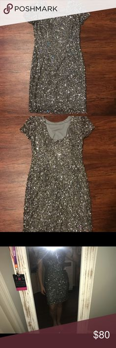Dark grey sequined dress with scoop back I absolutely love this dress! I bought it for a friends wedding and have only wore it once. It's more form fitted, and falls a little above my knee. It's a dark grey color with beautiful silver sequins all over! Adrianna Papell Dresses