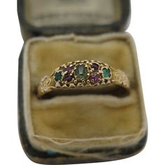 An English Victorian Ladies  15K Gold dress ring  set with small spinel rubies and  emerald's.The shank has been chased with organic foliage and the