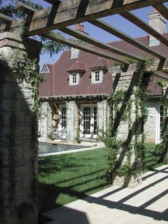 Stone pillars in the pretty backyard of a gorgeous stone English cottage-style house:)